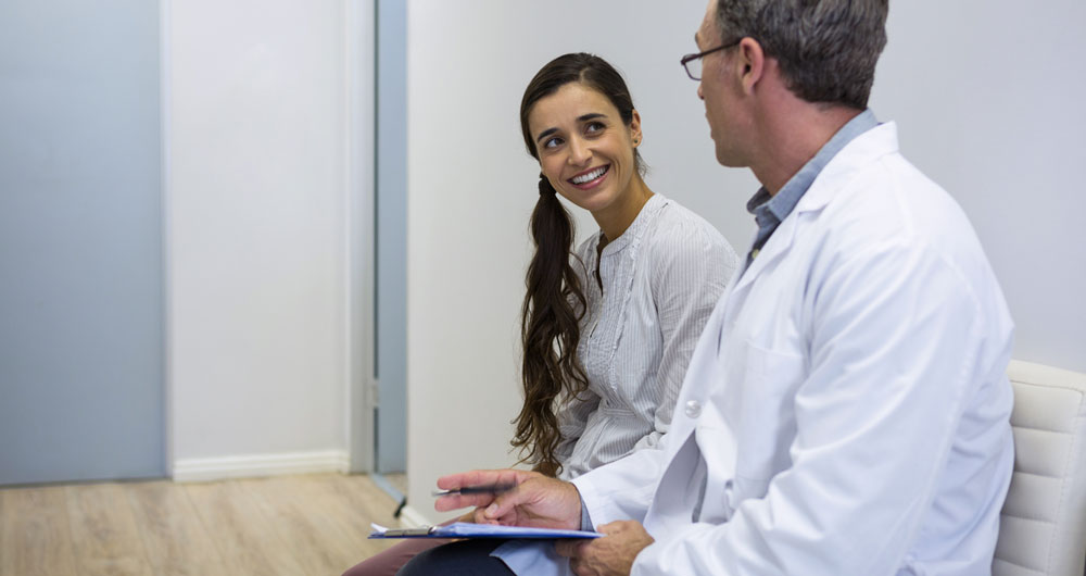 a young woman discusses medically assisted treatment with a doctor