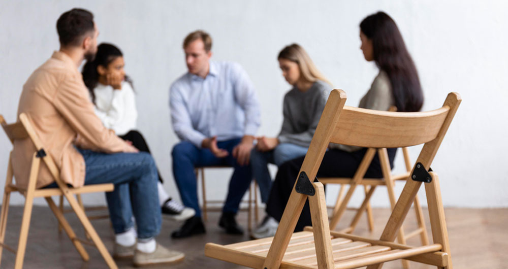 an empty chair in a room of people taking part in a group therapy session