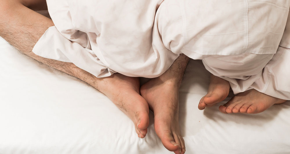 two bare feet under the covers in bed