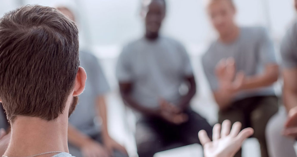 a group of men take part in an intensive group therapy session