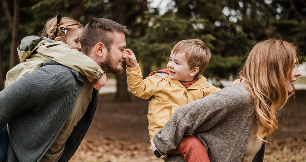 a young mother and father play outdoors with their two young children