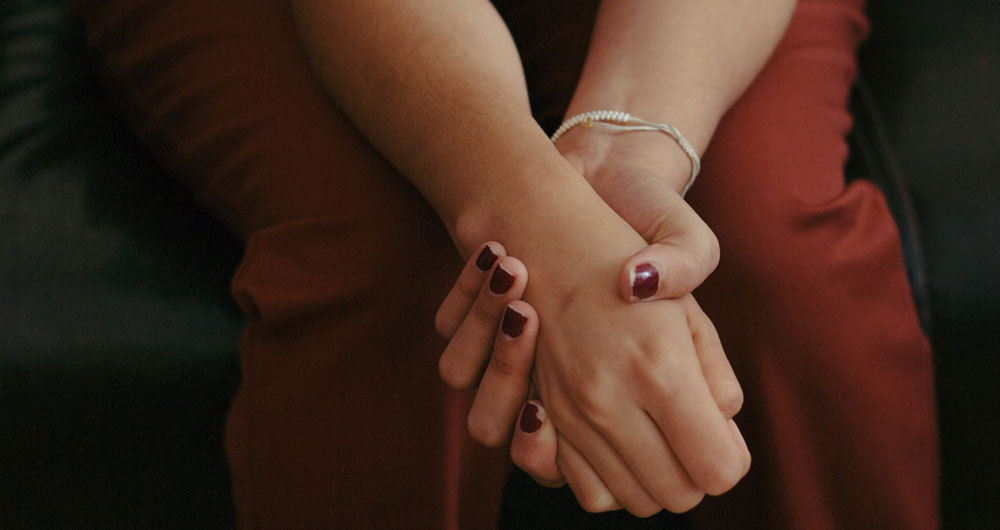 young woman clasps hands together